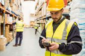 Focused worker wearing yellow vest using handheld in a large warehouse