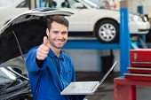 Mechanic using his laptop showing thumbs up at the repair garage