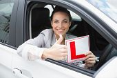 Female driver giving thumbs up while holding her L sign in her car