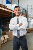 Portrait of smiling male manager with arms crossed in warehouse