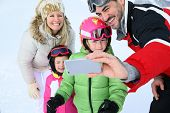 stock photo of family ski vacation  - Family taking picture at the top of ski slope - JPG