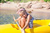 Adorable little girl enjoy kayaking during summer vacation