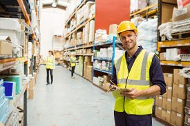 image of warehouse  - Warehouse worker smiling at camera with clipboard in a large warehouse - JPG