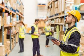 pic of warehouse  - Focused warehouse manager writing on clipboard in a large warehouse - JPG