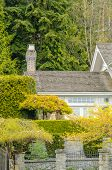 image of nice house  - The roof of the house with nice window and outdoor landscape with stone fence - JPG