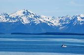picture of mountain-range  - snow capped mountain range towers over commercial fishing boat in the foreground - JPG