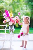 foto of windows doors  - Little girl arranging flowers at home in a vase - JPG
