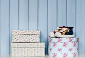 stock photo of shoe-box  - tiny shoes and old vintage boxes for storage on the bookshelf on blue wooden background - JPG