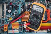 stock photo of  multimeter  - Digital multimeter and circuit board shot close - JPG