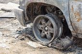 stock photo of fire insurance  - Close up front left wheel of a burnt car in fire situation insurance matter - JPG