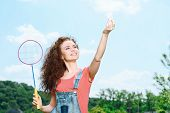 picture of shuttlecock  - Portrait of a young beautiful lady standing in a park holding a racquet above her and a shuttlecock in another hand - JPG