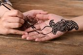 picture of mehndi  - Process of applying Mehndi on female hand close up - JPG