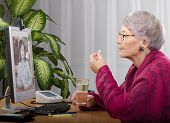 picture of telecommuting  - Old woman taking antidepressant pill during medical consultation online - JPG