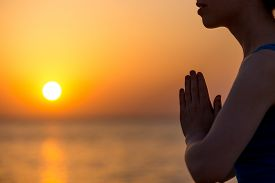 stock photo of breathing exercise  - Profile of serene young woman relaxing on the beach meditating with hands in Namaste gesture at sunset or sunrise close up - JPG