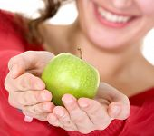 girl holding an apple with her hands while smiling - focus is on apple