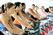 stock photo of gym workout  - Group Of People Cycling In A Gym - JPG