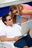couple using a laptop while relaxing by the swimming pool