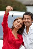 Couple holding up the keys of their brand new car poster