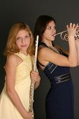 image of music instrument  - teenage sisters with flute and trumpet and wearing prom dresses - JPG