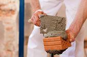 pedreiro colocar tijolos, fazer uma parede, ele está colocando argamassa em cima de um tijolo
