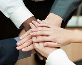 Close-up of people with hands together. Concept of union in business