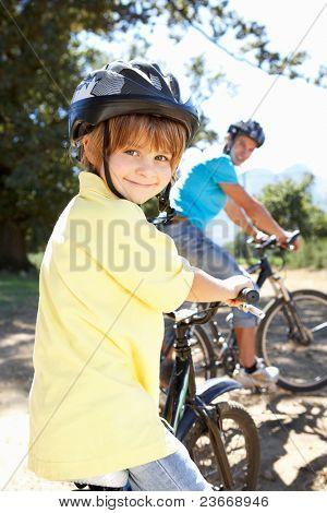 Постер, плакат: Маленький мальчик на велосипеде страны ездить с отцом, холст на подрамнике