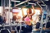 Young Woman Training Back With Weight-lifting Training Machine poster