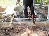 Construction Workers Pouring Water To Reinforcement Wooden Framework. Preparing Building Site. poster