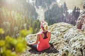 Young Girl Traveler Sits On Top Of A Mountain In A Yoga Pose. The Girl Loves To Travel. Concept For  poster