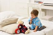 Child In Bedroom With Silence Gesture. Time To Sleep Concept. Boy With Happy Face Puts Favourite Toy poster
