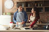 Happy Young Woman And Man Baking Pie In Loft Kitchen. Young Family Cooking At Home, Using Digital Ta poster