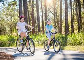Two kids enjoying a fun bicycle ride together on a bike path in a green forest outdoors. Smiling and poster