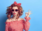 Pinup Portrait Beauty Redhead Girl Blowing Lips. Fashion Playful Woman Showing Ok Sign. Presenting Y poster
