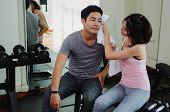 Muscular Young Handsome Man Helping Wipes Sweat Off Young Asian Woman Face While Resting After Worko poster