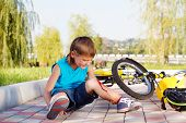 stock photo of scabs  - Crying boy with a bleeding injury sitting beside the bike that he has fallen from - JPG