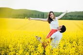 Portrait Of Happy Young Family Couple Feel Happiness And Freedom, Pose Together At Yellow Meadow Aga poster