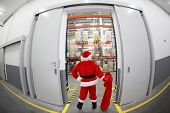 Santa Claus with empty sack doing wholesale shopping. At the gate to Gifts Distribution Center