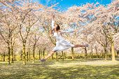 Happy Teenager He Is Laughing And Jumping Up. Teen Girl In Spring Blossoming Garden. Teenager And Bl poster