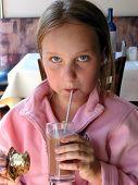 Girl Drinking Chocolate Milk In A Restaurant