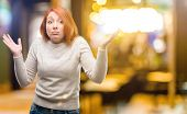 Beautiful young redhead woman doubt expression, confuse and wonder concept, uncertain future shruggi poster