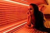 Happy Young Woman Sunbathing In A Solarium Under Ultraviolet Rays, Wants A Beautiful Tanned Skin poster