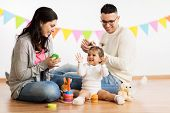 family, holidays and people concept - happy mother, father and little daughter with toys playing and poster