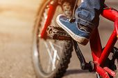 Detail Of Child Cyclist Feet Riding Bike On Outdoor In Sunny Road. Closeup On Pedal And Foot. poster