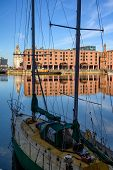 Tall Shot Of The Albert Dock In Liverpool Through The Rigging Of A Small Boat Moored At The Side poster