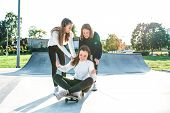 Three Teenage Girls Teenagers Ride A Skateboard, Happy Have Fun Playing And Laughing, In The Summer  poster