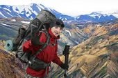 Happy Traveler Equipped With A Red Jacket On The Hillside Raised In Greeting Hand. Beautiful And Col poster