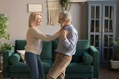 Active Funny Elderly Wife And Husband Dancing At Home poster