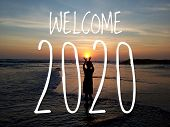 Welcome 2020. New Year Concept With Young Girl Silhouette Standing Holding The Sun In The Beach Back poster