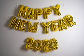 Celebrating The New Year 2020. Gold Foil Balloons On A Gray Background. Foil Balls, Festive Concept  poster
