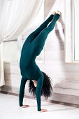 Curly Brunette In A Green Sportswear With A Elegant Slim Figure Stands In Her Arms Upside Down, Asan poster